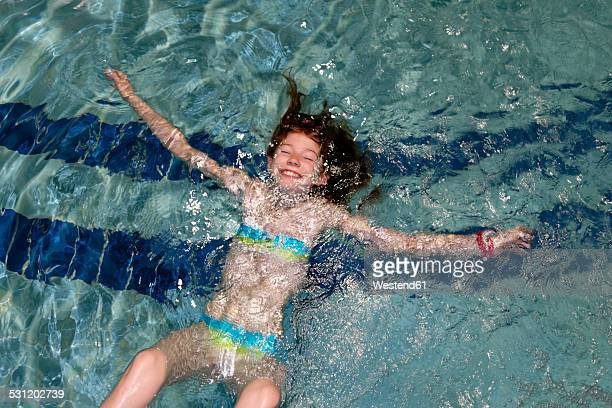 Smiling girl swimming backstroke in a pool