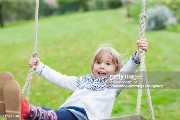 Smiling girl swinging in backyard