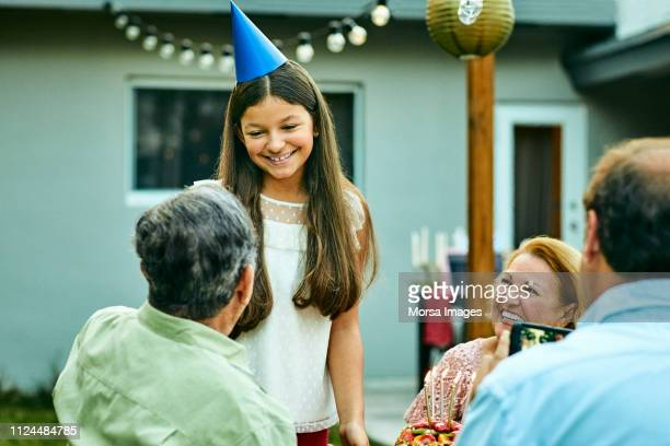 smiling girl talking to grandfather at back yard - celebration fl stock pictures, royalty-free photos & images