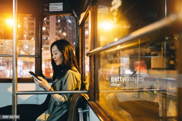 Smiling girl text messaging on mobile phone while riding on tram in the city