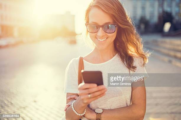 smiling girl texting at the street - instrument of time stock photos and pictures