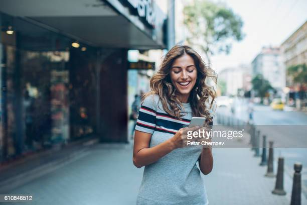Smiling girl texting on the street