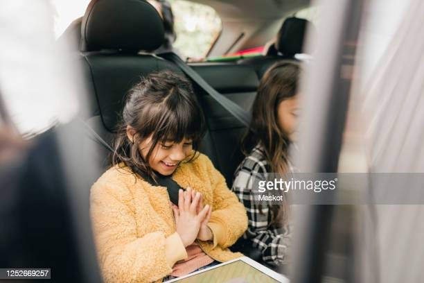 smiling girl using digital tablet while sitting in car - 車内 ストックフォトと画像