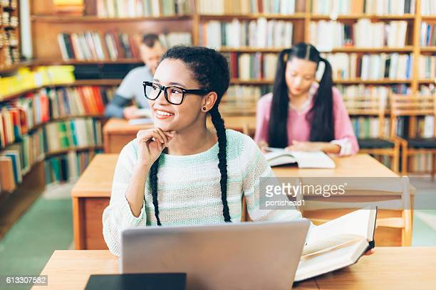 Smiling girl using laptop at library