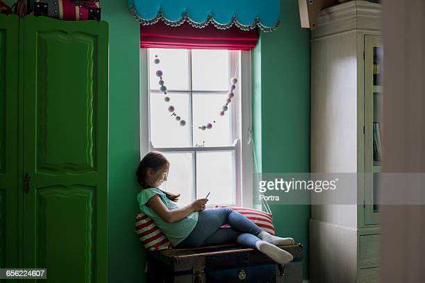 Smiling girl using mobile while sitting by window