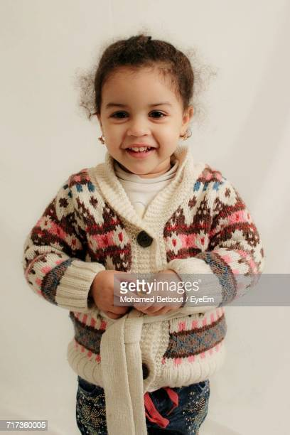 Smiling Girl Wearing Cardigan Sweater Against Wall