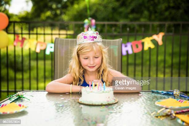 smiling girl wearing crown looking at birthday cake on table in backyard - happybirthdaycrown stock pictures, royalty-free photos & images