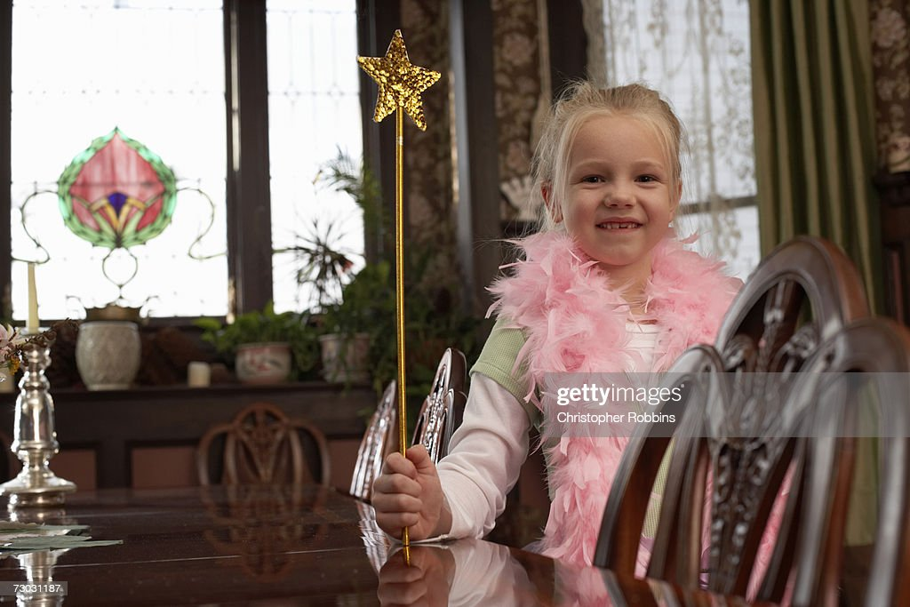 Smiling girl (6-7) wearing feather boa holding magic wand in living room : Stock Photo