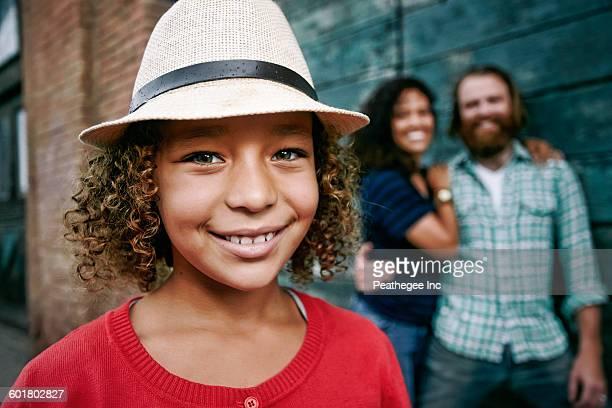 Smiling girl wearing fedora outdoors