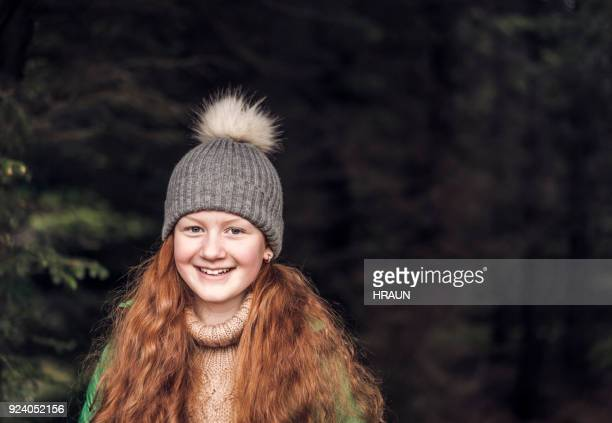 smiling girl wearing knitted hat in forest - gray hat stock pictures, royalty-free photos & images