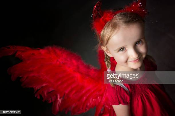 smiling girl wearing red costume wings and devil horn headband - devil costume stock photos and pictures