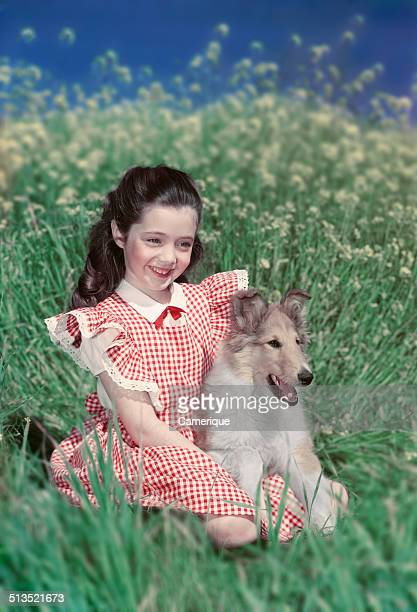 Smiling girl wearing red gingham checked dress sitting in field with collie dog puppy Los Angeles California 1949