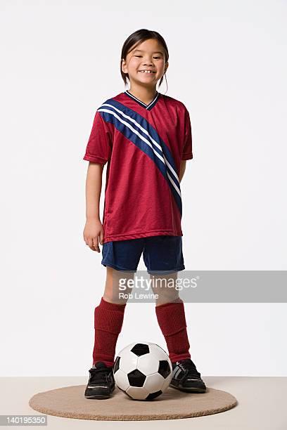 Smiling girl (8-9) wearing soccer uniform, studio shot
