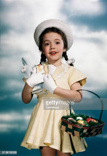 Smiling girl wearing yellow dress straw hat holding toy rabbit and easter basket Los Angeles California 1949