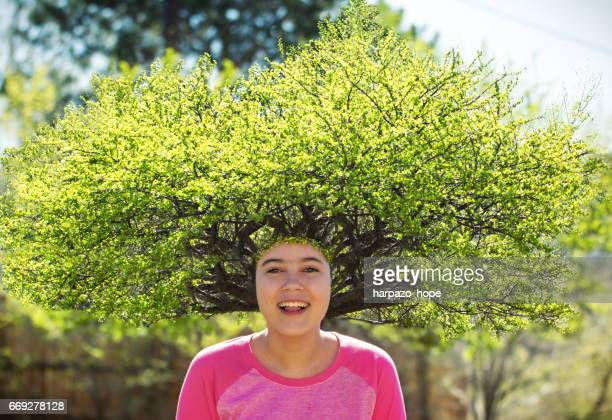 Smiling girl with a tree for hair.