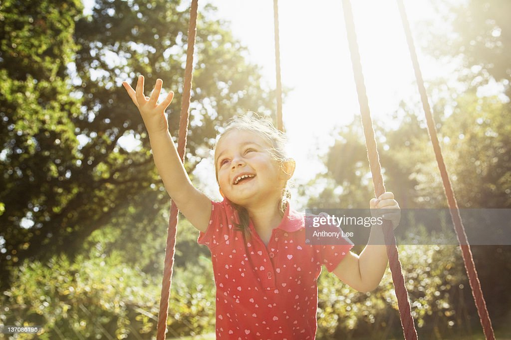 Smiling girl with arm outstretched on swing in sunny park : Stock Photo