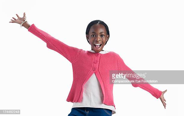 Smiling girl (11-12) with arms outstretched