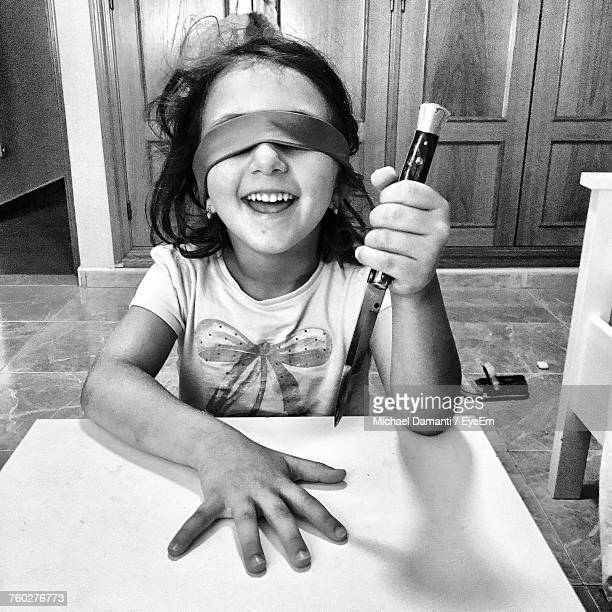 smiling girl with blindfold holding knife while sitting on floor at home - michael damanti fotografías e imágenes de stock