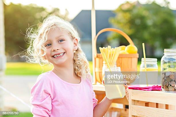 Smiling girl with blonde curly hair holding up lemonade