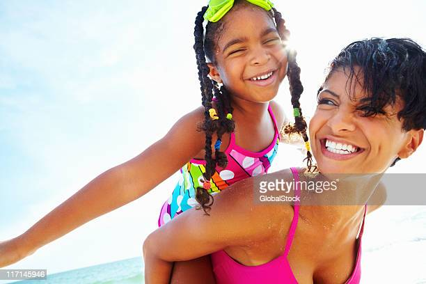 Smiling girl with braids carried piggyback style by woman