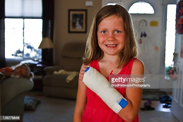 Smiling girl with broken arm in cast