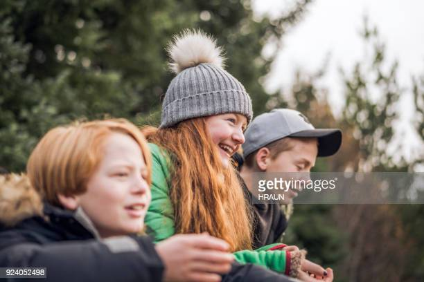 smiling girl with brothers relaxing in forest - weekend activities stock pictures, royalty-free photos & images