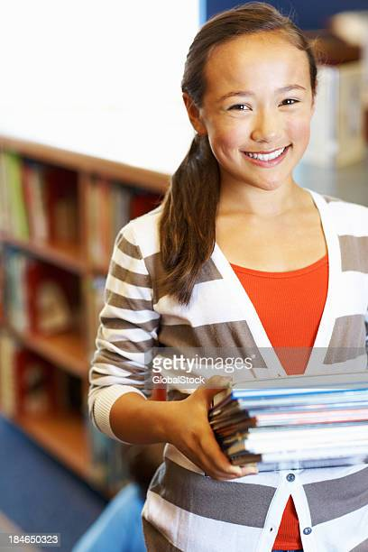 Smiling girl with carrying stack of books