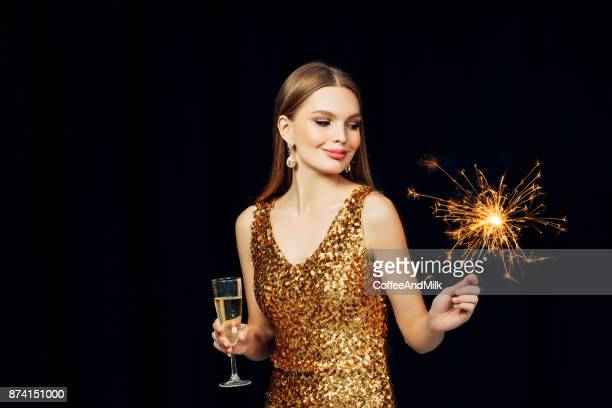 smiling girl with christmas sparkler - gold dress stock pictures, royalty-free photos & images