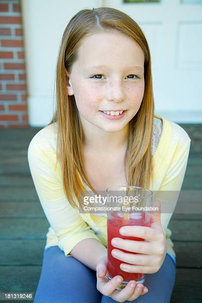 Smiling girl (10-11) with drink outdoors