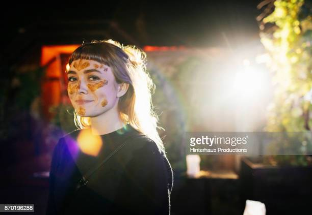 Smiling Girl With Gold Glitter Face Paint At Nightclub
