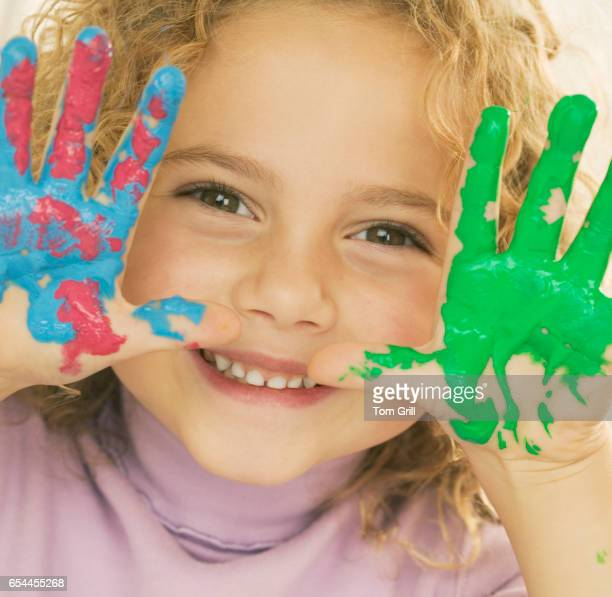 smiling girl with hands covered in paint - 4 girls finger painting stock photos and pictures