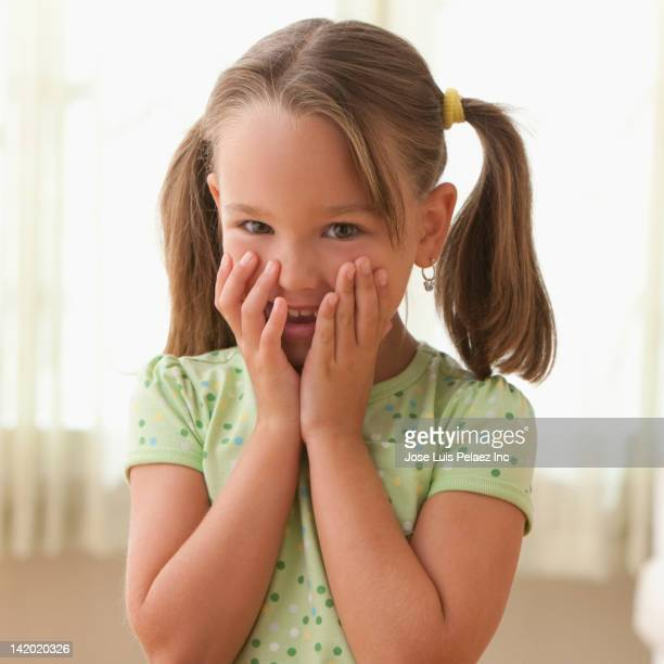 Smiling girl with hands covering face