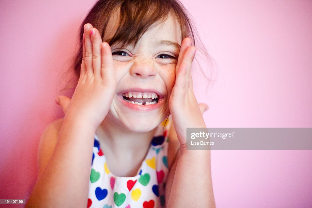 Smiling girl with hands on face : Stock Photo