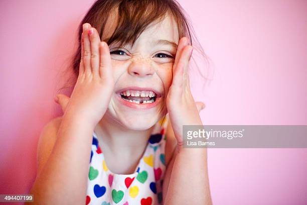 Smiling girl with hands on face