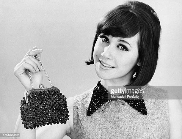 """Smiling girl with her hair dressed in a bob shows at the camera a classic jais clutch purse with handle made of chain, suitable for the evening...."
