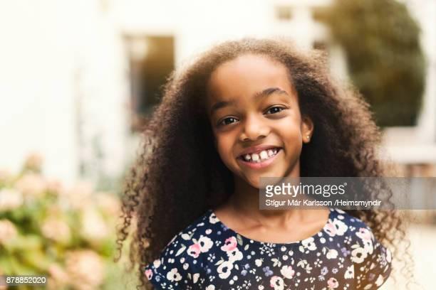 Lächelndes Mädchen mit langen lockigen Haaren in geblümten Kleid