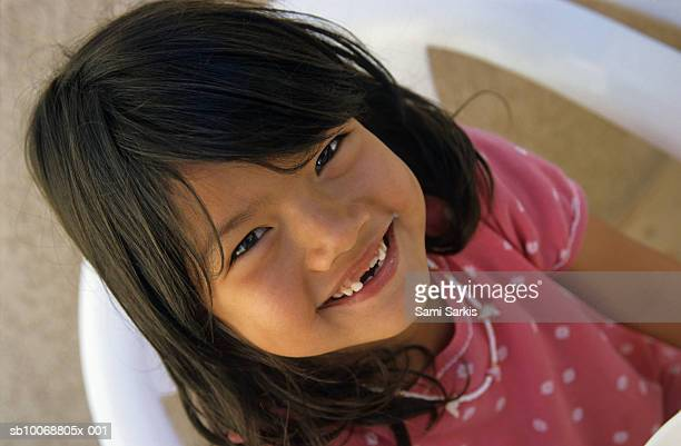 Smiling girl (6-7 years) with missing teeth sitting on chair, elevated view, close  up, portrait