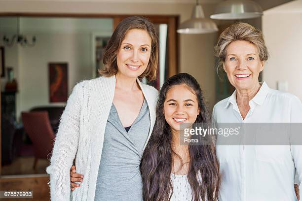 Smiling girl with mother and grandmother at home
