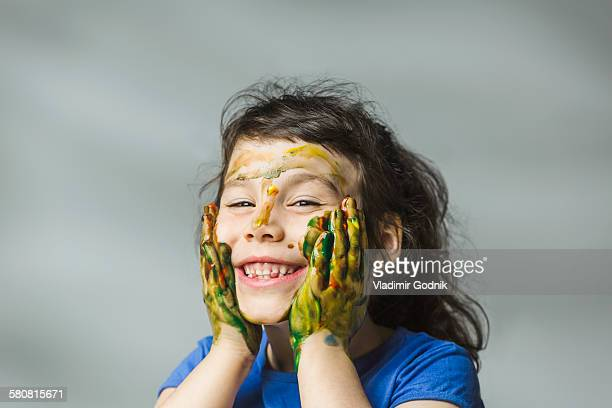 Smiling girl with painted face and hands over gray background