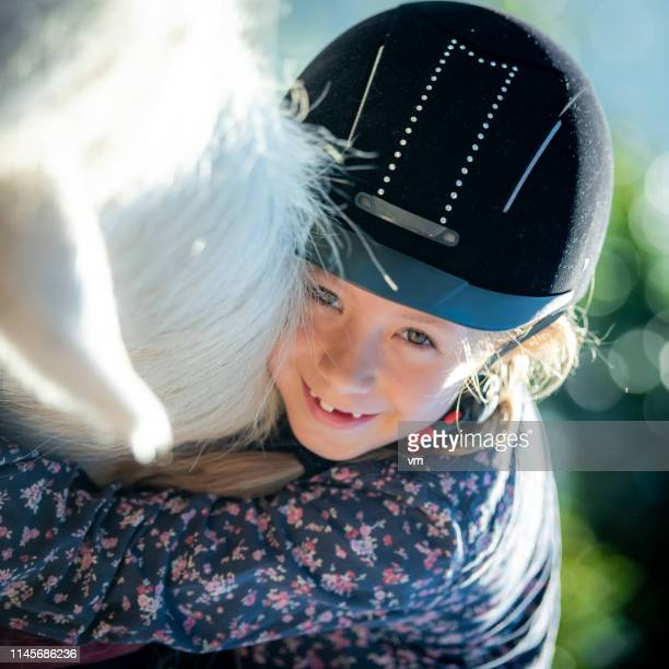 smiling girl with riding helmet looking at camera - riding hat stock pictures, royalty-free photos & images