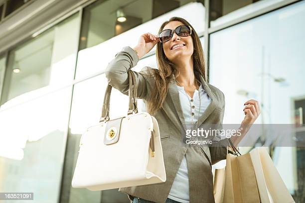 smiling girl with shopping bags - clutch bag stock pictures, royalty-free photos & images