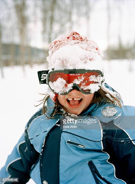 A smiling girl with snowy ski goggles.