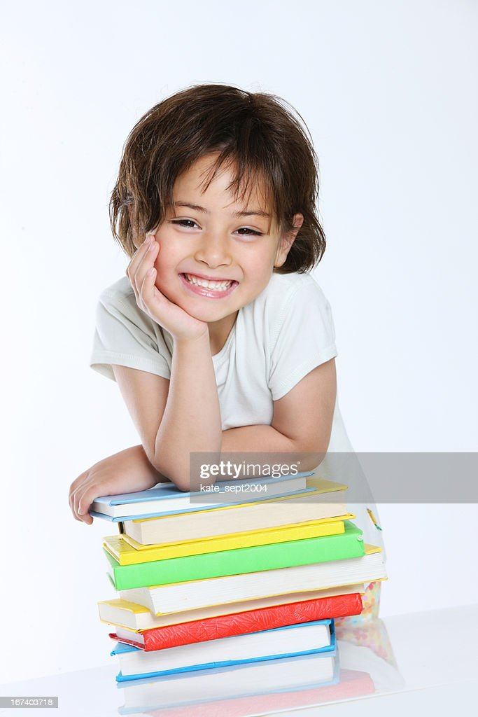 Smiling girl with stack of books : Stock Photo