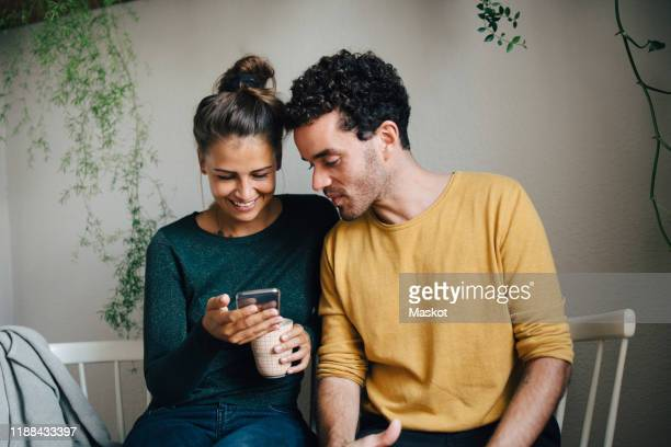 smiling girlfriend showing smart phone to boyfriend while having coffee in living room - heterosexual couple stock pictures, royalty-free photos & images