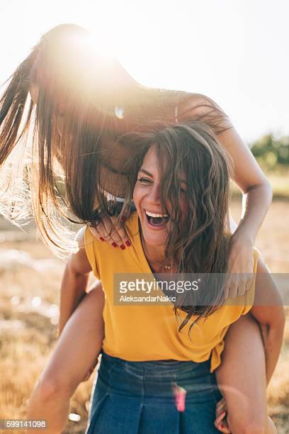 Smiling girlfriends having fun in piggyback ride