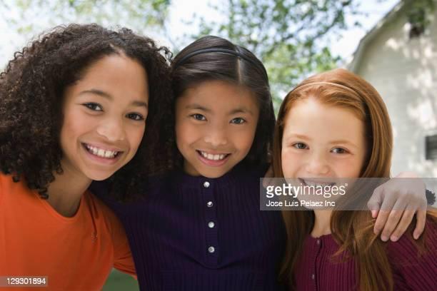 smiling girls hugging outdoors - multiculturalismo foto e immagini stock