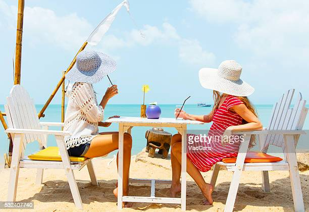 smiling girls in cafe on the beach