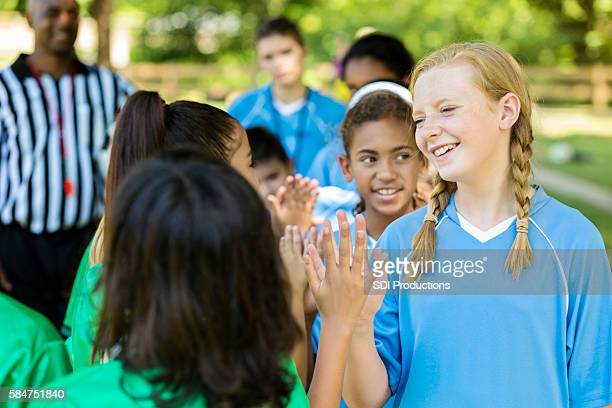 smiling girls in high five line after great soccer game - kick line stock photos and pictures