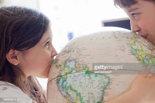Smiling girls kissing globe indoors