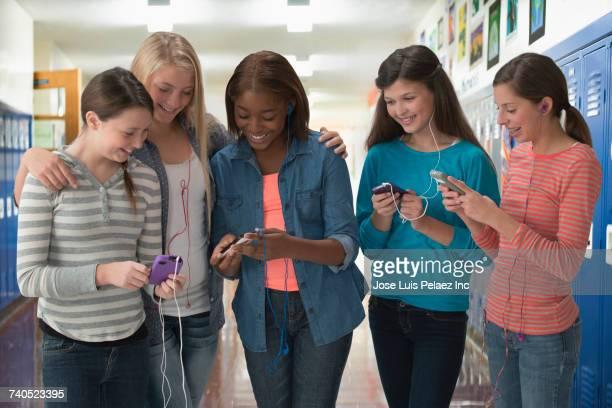 Smiling girls listening to cell phones in school corridor